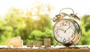 שעון מטבעות ומיניאטורה של בית על רקע טבע